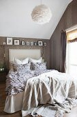 Bed with upholstered headboard under sloping ceiling in attic bedroom with patterned wallpaper and shelf of pictures