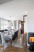 Set table, upholstered chairs, log burner and firewood store in dining room