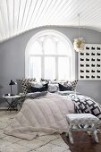 Attic bedroom with Gothic window and mixture of patterns
