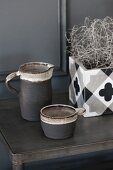 Grey jug and beaker next to planter with geometric pattern