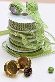 Gestapelte, hellgrüne Geschenkbänder und goldglänzende Kerzenhalter für Adventskranz