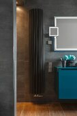 A dark grey heater between a shower and a petrol-blue washstand