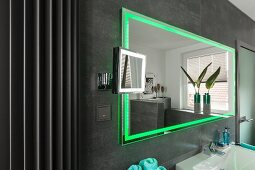 A wall mirror with integrated green LED lighting on a grey-tiled wall
