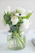 Glass vase of white spring flowers