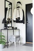 Delicate console table and coat rack in black and white foyer