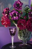 Purple, crystal liqueur glass next to vase of flowers in various shades of red