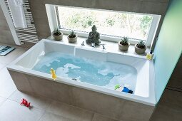 A bathtub filled with water and toys against a window in a modern bathroom