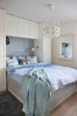 Wardrobes and wall-mounted cabinets framing bed headboard
