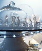 Glass nativity set on cake stand under glass cover