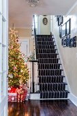 Wrapped gifts and straw horse below Christmas tree decorated in red and white next to staircase in country-house hallway