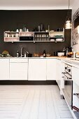 White fitted kitchen and shelves mounted on dark brown wall