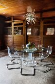 Metal and plexiglas chairs around glass table in former stable