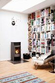 Log burner, floor-to-ceiling bookcases and reading armchair in cosy Scandinavian living area