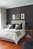 Scatter cushions arranged on double bed with tall, upholstered headboard against black wallpaper in elegant bedroom