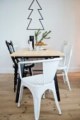 Dining table and various black and white chairs in front of outline of Christmas tree on wall