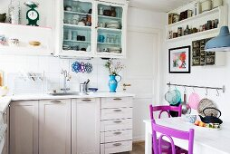 White-painted, L-shaped, country-house-style kitchen counter and wooden chairs painted purple in dining area in foreground