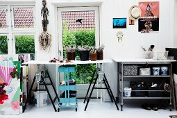 Work table on trestles above turquoise-painted trolley with shelves in front of terrace door