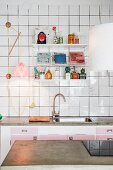 View across concrete worksurface to String shelving unit on white-tiled wall above kitchen counter