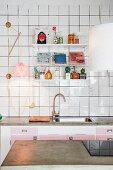 Blick über Arbeitsplatte aus Beton auf weiss gefliester Wand mit String-Regal über Küchenzeile
