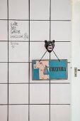 Retro Küchenschild auf einem Haken mit Pantherkopf-Motiv an weisser Fliesenwand