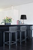 Flower arrangement and table lamp on counter with black-painted, metal barstools with backrests