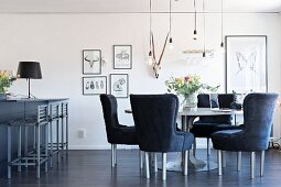 Grey upholstered chairy around round table below suspended bulb-style pendant lamps in open-plan living area with breakfast bar