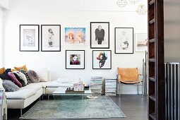 White corner sofa and glass coffee table on rug in modern living room with gallery of pictures on wall