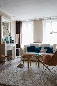 Classic furniture, fireplace and blue scatter cushions in bright, pleasant living room