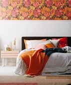 Double bed with orange color accents, floral wallpaper over white base