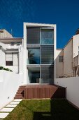 A view from the garden on a sunny wooden terrace of a contemporary, multi-storey town-house