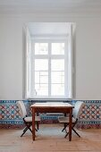 Table and upholstered chairs below window; dado strip covered with hand-painted tiles