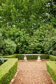 Stone bench in antique Greek style in landscaped garden with hedges