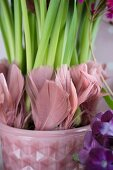 Dusky pink feathers decorating stems of flowers planted in retro flower pot