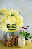 Bouquet of tulips in glass jar next to purple crocus and daisies planted in bowls