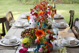 Rustic wooden table set with glasses of aperitifs and vases of autumn flowers