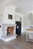 Open fireplace with stone surround next to modern, black fridge-freezer in white, wood-clad, country-house kitchen