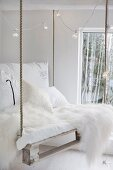 White sheepskin, white cushions and fairy lights on DIY pallet swing