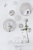White, festive wall decorations above candelabra and glass vase on side tablee