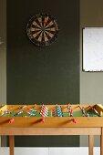 Table football table below darts board on green wall