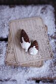 Pine cones decorated with white paint on old fashioned sheet music