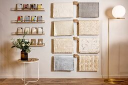 Side table below postcards on narrow shelves and sheets of wrapping paper hung from rods next to elegant standard lamp