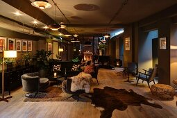 Spacious lounge with various illuminated seating areas on rustic wooden floor with animal-skin rugs; cosy ambiance