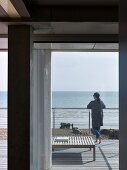 View from house through open French window; woman leaning on terrace balustrade looking out over sea