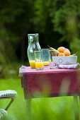 Refreshing drinks and bowl of fruit on garden table with purple runner