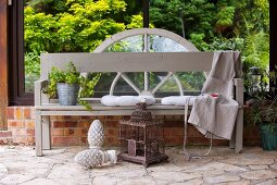 Garden bench painted pale grey on terrace against glazed side wall behind vintage birdcage and garden ornament on stone floor