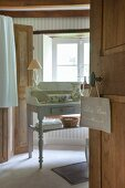 Sign hung on bathroom door and view of wash basin and pitcher on vintage table