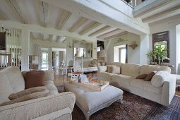 Pale sofa set and ottoman in open-plan living area of renovated country house with white-painted wood-beamed ceiling
