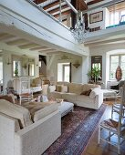 Pale sofa set on Oriental rug in living area below gallery in renovated country house with white-painted wood-beamed ceiling