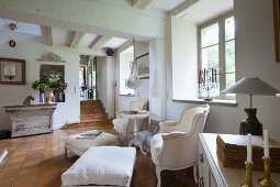 Two Rococo armchairs and footstools with pale covers below window in rustic living room with terracotta-tiled floor
