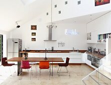 Minimalist table with wooden top and chairs with various covers in open-plan designer kitchen